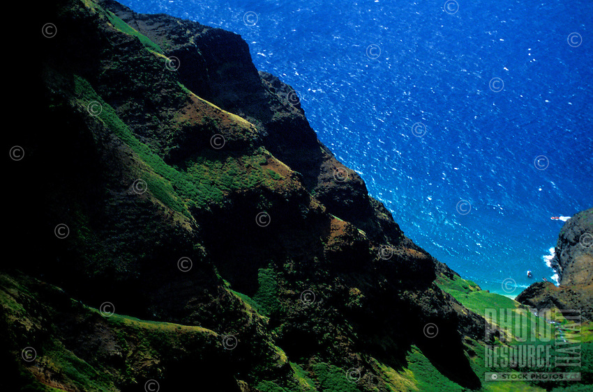Aerial view of Kauai's Na Pali coastline with zodiac tour boats rounding the point