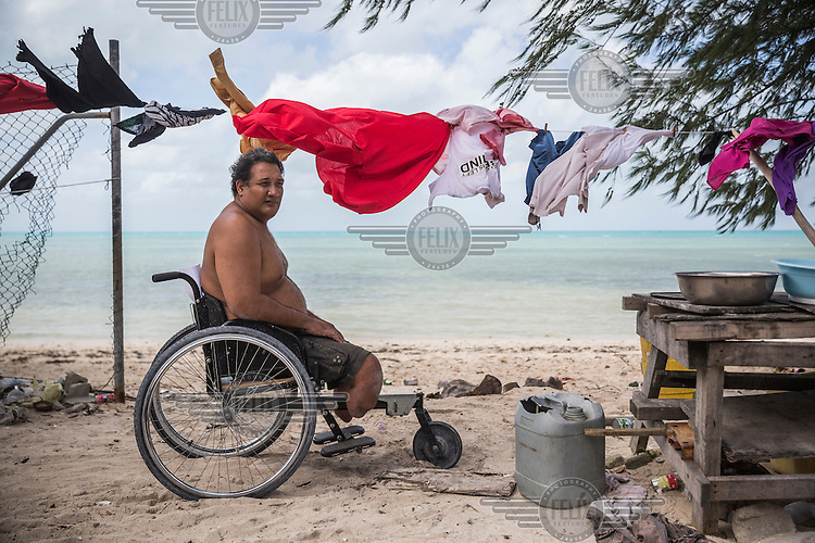 Karea Tioti, 46, a member of Te Toa Matoa Disability Organisation on his on a tricycle wheelchair on a beach near the 'maneaba', a traditional I-Kiribati community house, where all members of the organisation sleep at night.<br /> <br /> Karea says: 'Every time during King tides, when the sea water comes, we are not prepared. We don't really know where to go, so we stay inside our 'maneaba'. Sometimes water covers our floor and makes our things wet. But the main problem for us is water around our 'maneaba'. We get surrounded by the sea water and it's difficult for us to move around on wheelchairs or crunches, or for blind people to walk, to buy food or use a toilet. We just stay inside and wait for a few days till the water goes back to the sea. Usually this happens once a year, but in 2015 this happened two times. We have this fear that it will start happening more frequently.'