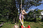 A girl plays on the swingset in her backyard in Reykjavik after a morning at the pool with her mother and younger sister.