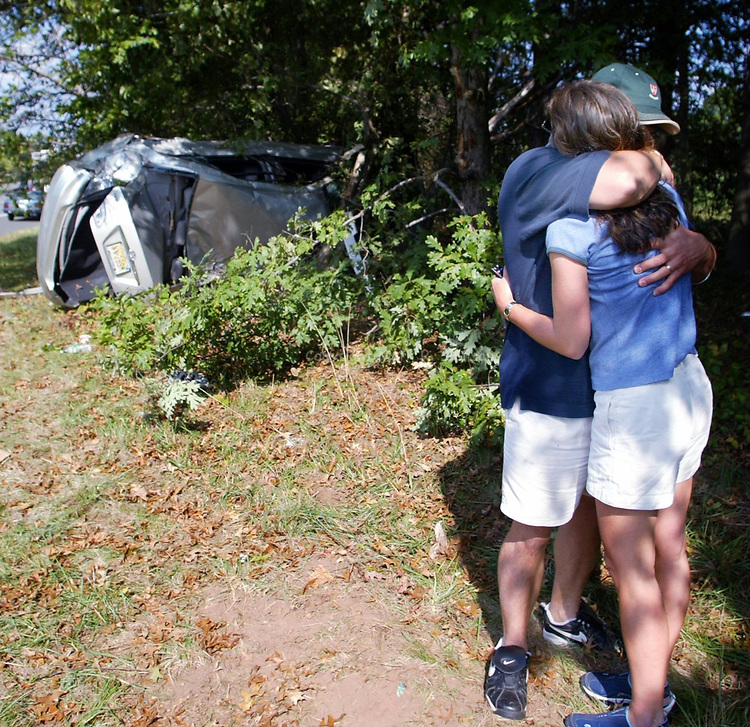 (mva)--27794-ON SAT OCT 05,2002-mva1005a--METRO--James Wilton hugs his wife after climbing from the wreckage of his over turned car after an morning accident that occured along the Garden State Parkway northbound at mile marker 130.3. Wilton was lucky he walked amway with minor scratches. (MARK R. SULLIVAN/HNT CHIEF PHOTOGRAPHER