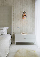 The master suite is a calm and tranquil space in off whites and neutrals. A winged headboard has been added to the super-king size bed, in a silver embossed faux animal skin fabric to gently frame the room, studded on the leading edges with rows of small chrome studs for definition. The walls are finished in softly textured vinyl wallpaper with hints of distressed wood cladding. Warmth was added by faceted copper glass pendant chandelier lights.