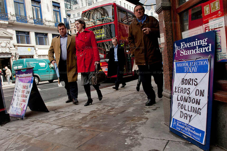 Pedestrians walk Fleet Street in front of a Red London Bus as signs for the evening Standard newspaper show Boris Johnston leading in the London Mayoral elections that took place on May 1st 2008 in London, UK