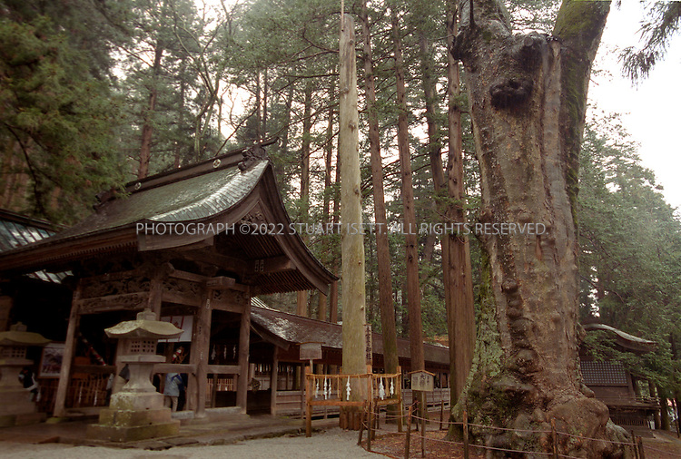 "4/2/2004--Suwa, Japan..A log from the previous Onbashira Festival stands tall inside the Shinto Shrine in Suwa...The basic purpose of the 1200 year old Onbashira Festival is rooted in Shinto, the indigenous religion of Japan. In the Shinto way of thinking, the Gods, or kami, are living in the natural environment which surrounds human beings. The Onbashira Festival serves as a reminder of the importance of nature to human beings: large fir trees (symbolic ""gods"") are brought down from the mountains, carried into town and set to stand at the outskirts of the Suwa Grand Shrine. In this way, the people of the Suwa region never completely lose their contact with nature and the gods, and they renew this contact at least once every 6 years through Onbashira Festival..Photograph by Stuart Isett.©2004 Stuart Isett. All rights reserved"