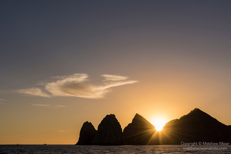 Sea of Cortez, Cabo San Lucas, Mexico; Lands End is silhouette against a sunset sky, these rocks at the southern most end of the Baja Peninsula separate the Sea of Cortez from the Pacific Ocean