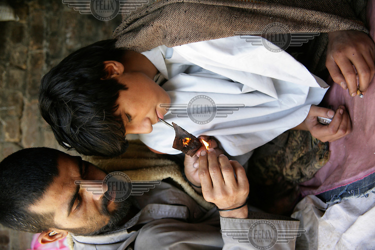 A man and boy smoke heroin outside the De Las Gul centre for drug users. UNICEF assisted with the establishment of the centre, and provides medical treatment, washing facilities and clean needles to addicts young and old. The centre also provides STD and HIV testing, and provides detox therapy alongside recreational activities. The ralationship between young addicts and older users is often highly controversial. 'Coupling' often occurs, where an older addict will provide a younger boy with heroin, in return for the money the younger boy brings in through begging. The relationships often become sexual, and boys are often 'dumped' after a few months and left to fend for themselves, once the older addict has found another boy....