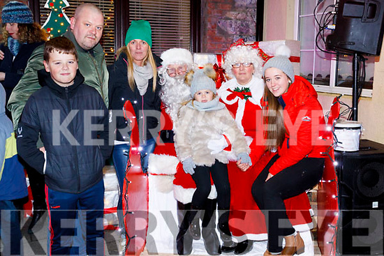 Molly Kate Mallon helped Santa push button to launch the Christmas lighting in Ballybunion on Sunday last. L-r Jack Mallon, Brian Mallon, Sharon Mallon, Molly Kate sitting on Santa lap, Mrs Claus and Kerrie Ann Williams Kissane.