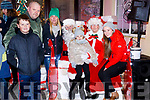 Molly Kate Mallon helped Santa push button to launch the Christmas lighting in Ballybunion on Sunday last. L-r Jack Mallon, Brian Mallon, Sharon Mallon, Molly Kate sitting on Santa lap, Mrs Claus and Kerrie Ann Williams Kissane.