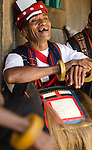 Man in traditional ceremonial dress sharing a laugh with friends. Luba Village, near Bajawa, Flores, East Nusa Tenggara, Indonesia