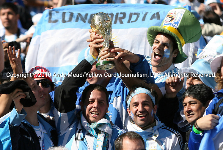 17 JUN 2010: Argentina fans hold a copy of the Jules Rimet Trophy. The Argentina National Team defeated the South Korea National Team 4-1 at Soccer City Stadium in Johannesburg, South Africa in a 2010 FIFA World Cup Group E match.