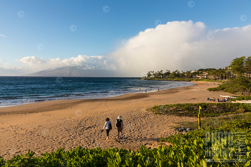 A woman and a man take a leisurely stroll in the afternoon sun at Wailea Beach, Maui; the West Maui Mountains can be seen in the distance.