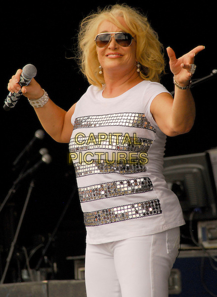 TANYA TUCKER.performs at the 2010 Jamboree In The Hills, Morristown, OH, USA, .18th July 2010..music country live concert gig on stage white silver striped top t-shirt microphone sunglasses half length .CAP/ADM/KB.©Kelly Blecher/AdMedia/Capital Pictures.