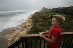 Conrad Burrus, 10, catches a burst of wind from Hurricane Ophelia on the oceanfront in Buxton.  Several residents gathered to see if the waves would roll over the re-enforced dunes.