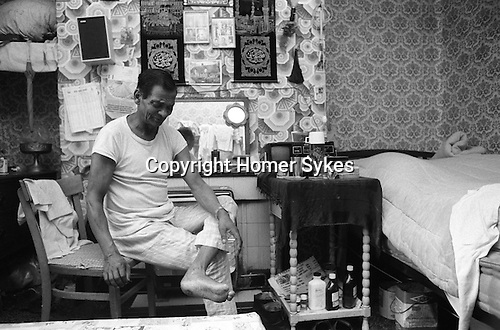 Invalid Asian male in bedsitting room that he shares with his wife  Blackburn Lancashire  1983