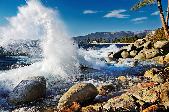 An image of a wave crashing into the rocky shorelilne of Lake Tahoe. A high wind preceding a storm created large waves and splashes on the east shore of Lake Tahoe on this day.
