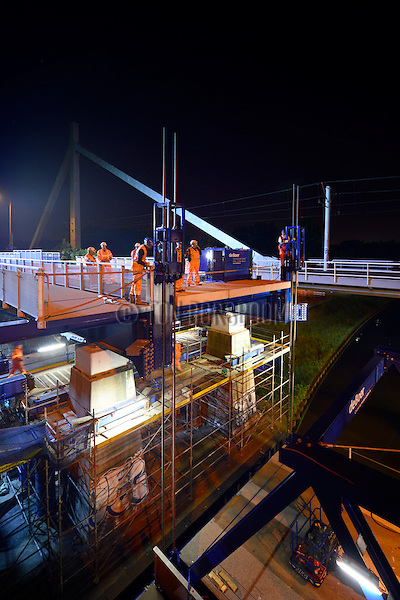 NIEUWEGEIN -  In het holst van de nacht heeft Rijkswaterstaat door Civiele Technieken deBoer – Spanlift een tijdelijke hulpbrug vanaf een ponton op de plaats van de weggeschoven Jutphasebrug over het Amsterdam-Rijnkanaal getakeld. De uit 1936 daterende boogbrug krijgt door bouwcombinatie KWS-Mercon een opknapbeurt en is een avond eerder op hoge hulppijlers verschoven waar later de stalen constructie versterkt, brugdek en pijlers gerepareerd en de brug opnieuw geverfd wordt. De Jutphasebrug zal naar een ontwerp van ingenieursbureau Movares volgend jaar 45 cm hoger worden teruggeschoven om hoger containervaart eronder mogelijk te maken. De renovatie van de Jutphasebrug is onderdeel van het project KARGO(Kunstwerken Amsterdam-Rijnkanaal Groot Onderhoud) waarbij acht stalen bruggen over het Amsterdam-Rijnkanaal, Lekkanaal en Buiten-IJ worden gerenoveerd en verhoogd. Op de achtergrond is de ernaast liggende trambrug zichtbaar die destijds al op de juiste hoogte was gebouwd. COPYRIGHT TON BORSBOOM