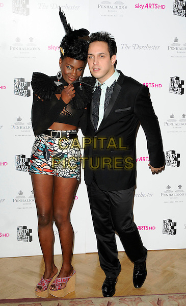 SHINGAI SHONIWA & DAN SMITH of The Noisettes.The South Bank Sky Arts Awards, The Dorchester Hotel, London, England, UK, 25th January 2011..full length black feather headband crochet cropped top shorts white red blue print wedges platform wood wooden suit hand.CAP/CAN.©Can Nguyen/Capital Pictures.