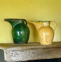 On the ancient kitchen mantelpiece two vivid 18th century tin-glazed earthenware jugs are juxtaposed against the deep yellow pigment of the walls