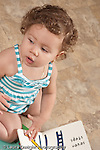 13 month old baby girl at home kneeling on floor hand on board book looking to side and vocalizing vertical