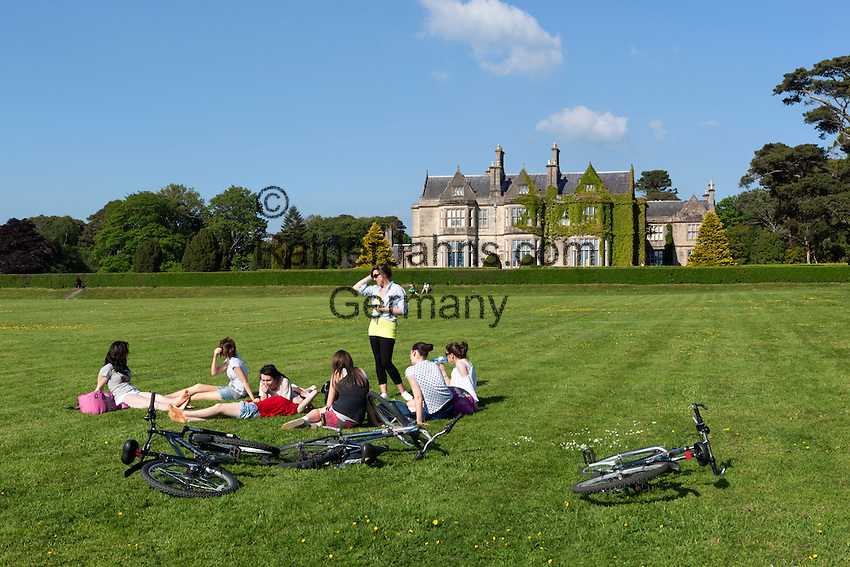 Ireland, County Kerry, near Killarney, Killarney National Park, Muckross House, 19th century Neo-Elizabethan stately home with young girls relaxing in grounds | Irland, County Kerry, bei Killarney, Killarney National Park, Muckross House, Gruppe junger Frauen ruht auf Wiese