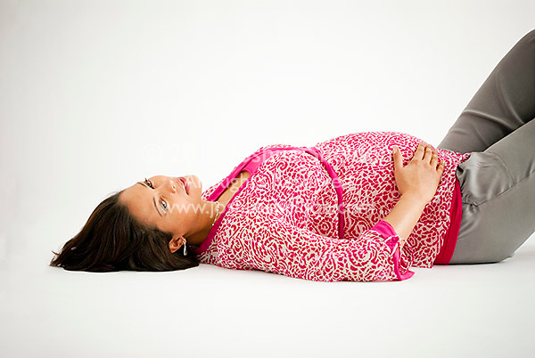 Pregnant Hispanic woman, laying down, hands on stomach
