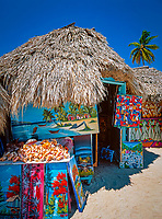 Dominikanische Republik, Isla Saona, Laguna Canto de la Playa, Holzhuetten, Verkauf einheimischer Malereien | Dominican Republic, Saona Island, Laguna Canto de la Playa, wooden huts, sale of native paintings