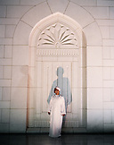 OMAN,  Muscat, young man standing by wall at night