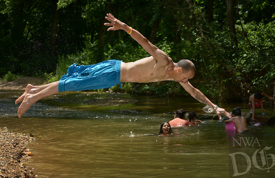 Javier Torres of Springdale dives in on Sunday May 29, 2016 while cooling off with his wife and children at Tanyard Creek Nature Trail in Bella Vista.