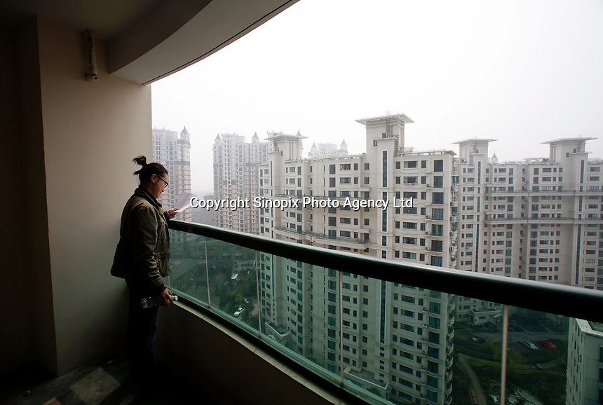 A young woman looks at the blueprint of her recently purchased apartment in Shanghai, China.. While real-estate developers' continued efforts to build for the high-end market push the overall housing price up, demand far outstrips supply on the low-end market in Shanghai and the average citizen find it hard to afford housing..25 Mar 2007