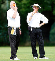 Match umpires enjoy a drink during the Middlesex County League Division Three game between Highgate and Bessborough at Park Road, Crouch End on Sat Sept 4, 2010