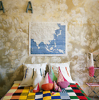 This teenager's bedroom has a simple, rustic feel with a distressed finish on the walls. The bed has a colourful knitted patchwork blanket and cushions in the shape of boats.