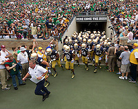 Head coach Brian Kelly leads the Irish onto the field.