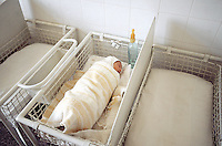 Bulgaria. Province Oblast Lovech. Lukowit. Hospital. Maternity ward. A new born baby, wrapped in a white blanket, sleeps alone in a bed. Baby's feeding bottle. © 1997 Didier Ruef