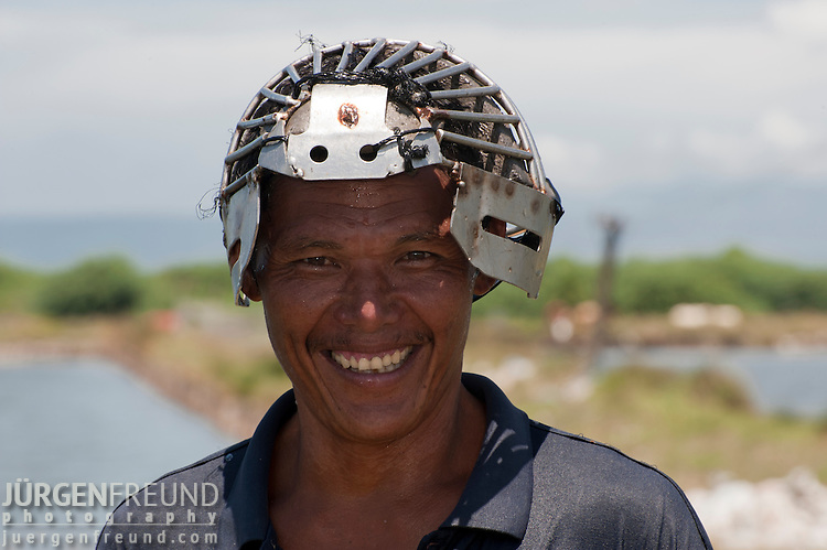 This courageous man with a groin and face guard made of stainless steel brings together the net to take out the milkfish (Chanos chanos) from the pond. Alsons Aquaculture.