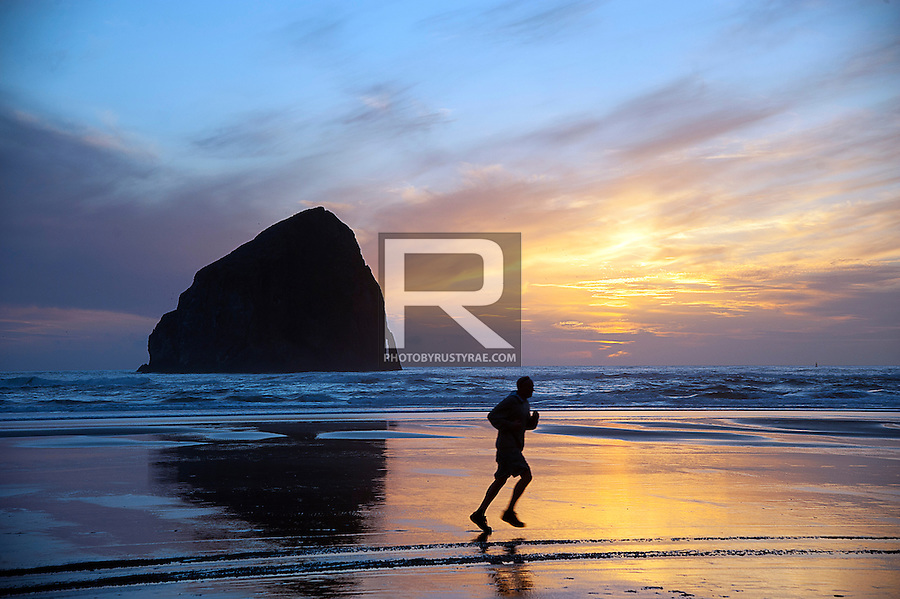 A runners finishes up his evening run on the beach at Pacific City as the sun sets with Haystack Rock in the background.