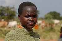 UGANDA Karamoja , Karimojong a pastoral tribe , young woman with facial ornament works as shepherd / UGANDA Karamoja , Volk der Karimojong , junge Frau mit Gesichtsverzierung und Schmuck aus Autoblinklicht und Tierherde