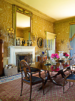 Lewis & Wood wallpaper with a floral pattern has been used in this dining room matched with a large Georgian mirror
