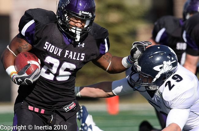 SIOUX FALLS, SD - NOVEMBER 13:  Jordan Taylor #26 from the University of Sioux Falls tries to shake the tackle of Ben Klein #29 from Concordia University in the second quarter of their game Saturday afternoon at Bob Young Field. (Photo by Dave Eggen/Inertia)