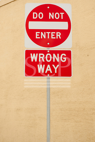 "California, USA. ""Do Not Enter"" and ""Wrong Way"" road signs in white writing on red background."
