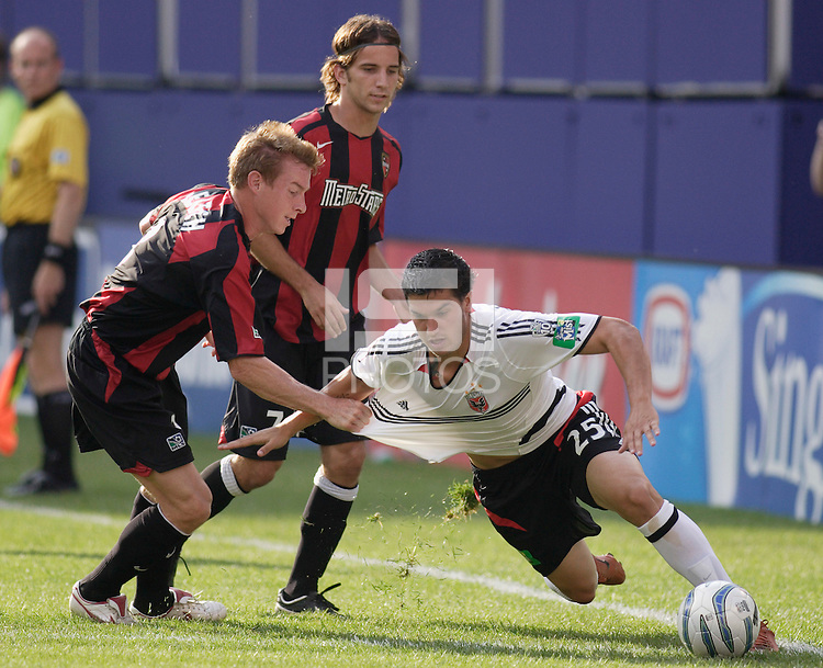 The MetroStars' Chris Leitch pulls down D.C. United's Santino Quaranta as Mike Magee watches. The MetroStars played D.C United to a 0 -0 tie at Giant's Stadium, East Rutherford, NJ, on June 12, 2005.
