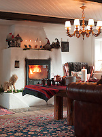 A roaring fire blazes in the wood burning stove in the living room, while a collection of felt gnomes perch on the mantelpiece above