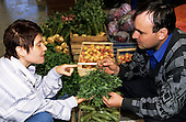Bucharest, Romania. Market trader discussing the use of tarragon with a customer; lots of fresh vegetables.