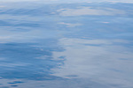 Clouds reflecting on the surface of the water on a calm day, Raja Ampat, West Papua, Indonesia, Pacific Ocean