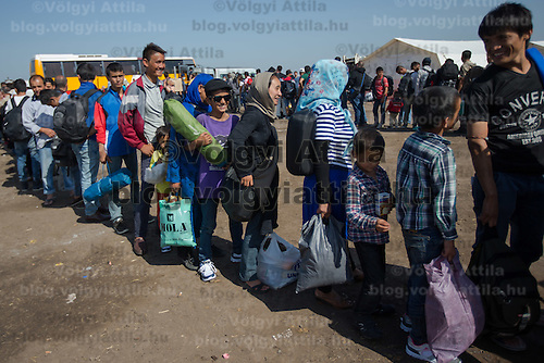 Illegal migrants get on buses after crossing the border between Serbia and Hungary near Roszke (about 174 km South of capital city Budapest), Hungary on September 14, 2015. ATTILA VOLGYI