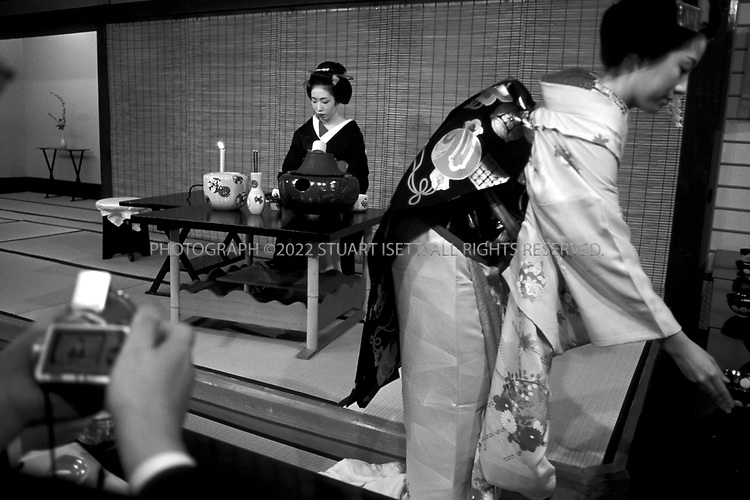 April, 2000--Kyoto, Japan..Geisha perform a tea ceremoney for camera toting tourists in the Gion..All photographs ©2003 Stuart Isett.All rights reserved.This image may not be reproduced without expressed written permission from Stuart Isett.