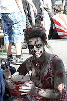 woman stirring a bowl with pretend blood, dressed in scars, from the zombie walk in prague, may 2014.