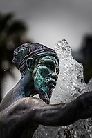 A close-up of the head and face on a water fountain sculpture of an Australian Aboriginal fisherman with the fountain's water rising behind.