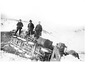 View of bottom of engine on its side in the snow at Osier.  3 workmen standing on overturned engine.<br /> D&amp;RG  Osier, CO  Taken by Payne, Andy M.