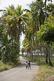 INDONESIA, Flores, kids walk down the road towards the beach and through the palms in the town of Riung