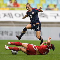 USWNT defender (2) Heather Mitts leaps over Canada's (14) Melissa Tancredi during the finals of the Peace Queen Cup.  The USWNT defeated Canada, 1-0, at Suwon World Cup Stadium in Suwon, South Korea.