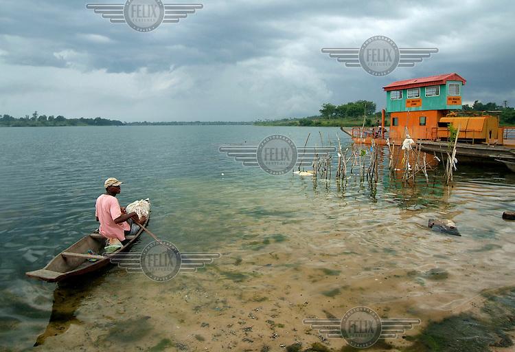 A man paddles a canoe at the margin of Oguta Lake.